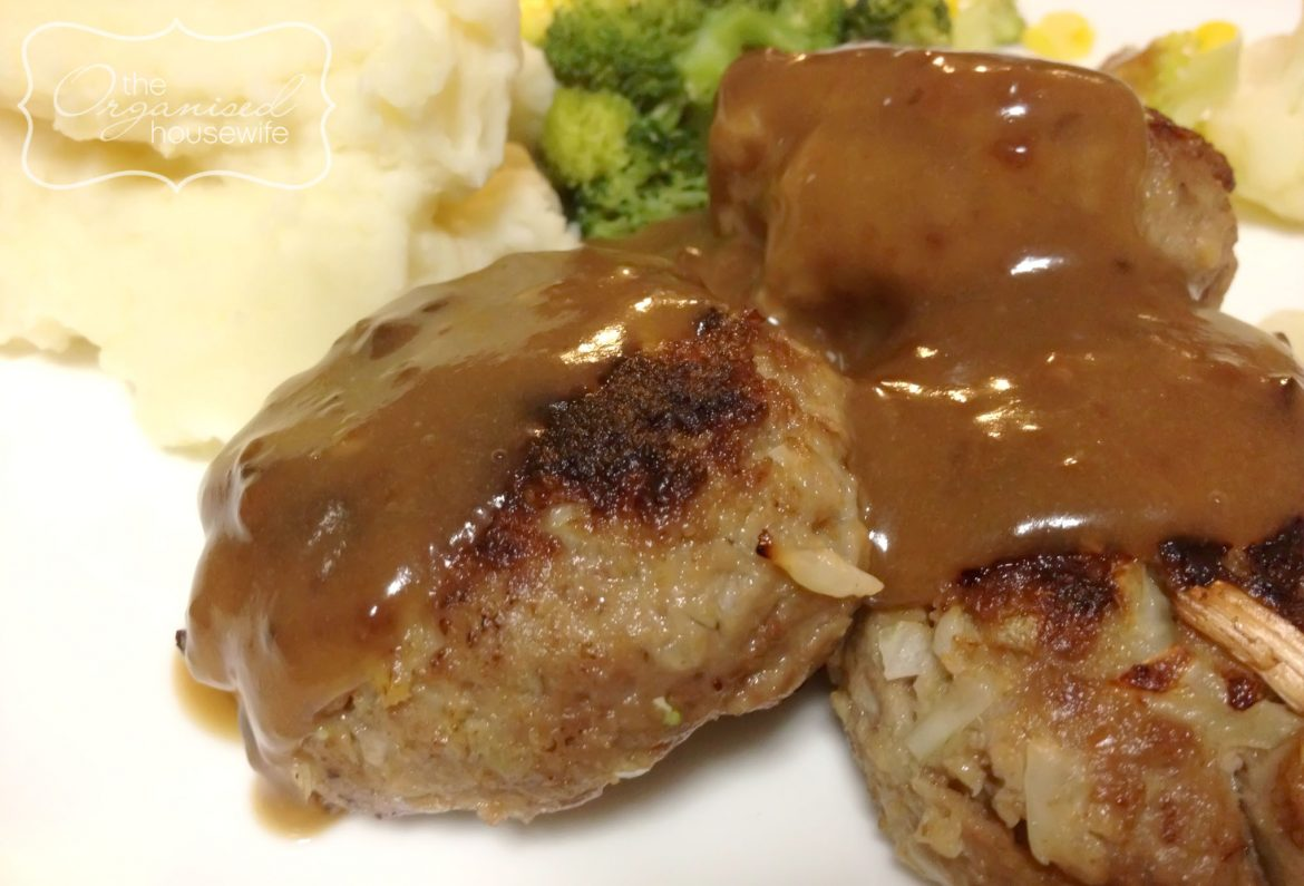 lamb rissoles topped with gravy with a side of vegetable and mash